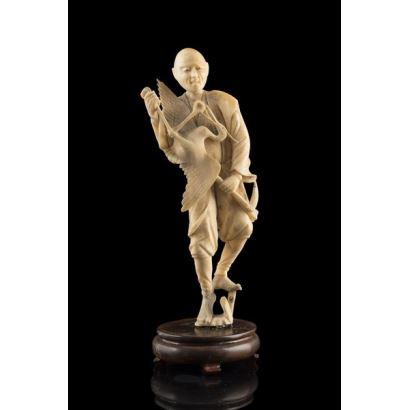 Talla de marfil (con Certificado de la Federación de Anticuarios) que representa a un personaje masculino con una garza en sus manos. 23x7cm