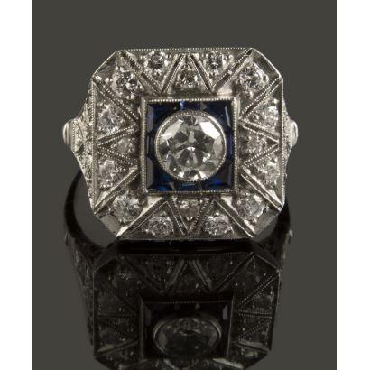 Extraordinario Anillo de platino con diamante central de 0,60cts. Rodeado de 0,90cts en diamantes y detalles en zafiros. Peso: 5,2gr