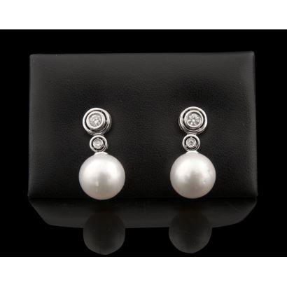 Elegantes pendientes de chatones en oro blanco, con dos brillantes de los que pende una bonita perla australiana. Brillantes: 0,45cts.
