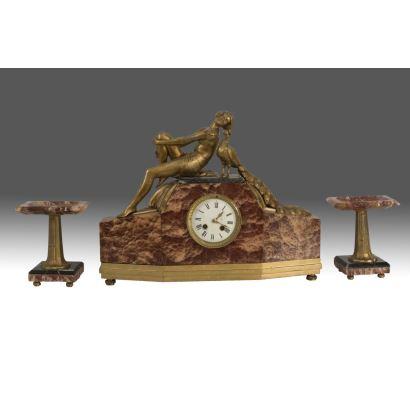 Elegante reloj de sobremesa de estilo Art Decó con dama y pavo real, con guarnición de copas en mármol rojo, primera mitad del s.XX.  Reloj:41x13x51cm. Copas: 18,5cm.