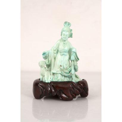 Figura china tallada en piedra turquesa sobre peana de madera.