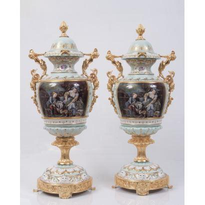 Elegante pareja de jarrones en porcelana policromada  y esmaltada con fondo verde, cuenta con pie y asas en bronce dorado, presenta dos escenas decorativas: