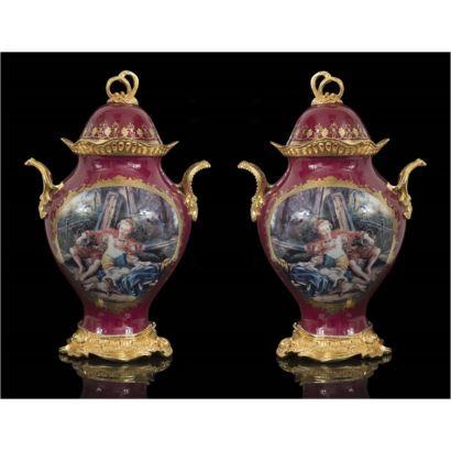 Pareja de jarrones de porcelana con tapa y doble asa, con detalles dorados al oro fino, con fondo granate con medallones decorados por escenas galantes. Medidas: 40x24cm.