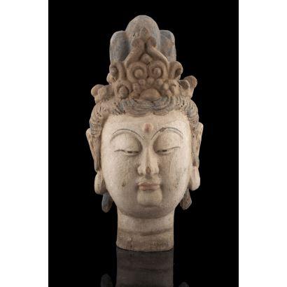 Excepcional cabeza de Buda tallada en madera maciza, siglo XIX, parcialmente policromada. Leves desperfectos. Medidas: 46x23cm.