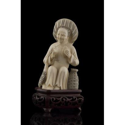 Figura tallada en marfil sobre peana de madera, dotada de gran expresividad.