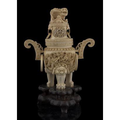 Importante brasero ceremonial en marfil sobre peana de madera, con profusa decoración de dragón sobre patas de garra sobre bola, con tapa decorada con perros de Fo. Con certificado de antigüedad. Medidas: 26x18,5cm.