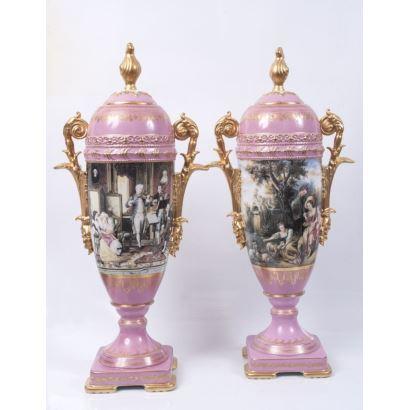 Pareja de estilizados jarrones en porcelana esmaltada, presentan franja central con escena de concierto y pastoril sobre fondo rosa, detalles dorados en asas y tapa. Marca en base. Medidas: 88x22x22cm.