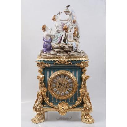 Reloj de sobremesa en porcelana policromada y bronce dorado, rematado en grupo escultórico mitológico.
