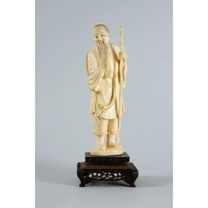 Escuela japonesa, PPIOS S. XX. Okimono representando a anciano con bastón. Realizado en marfil tallado sobre peana de madera. Con certificado de antigüedad. Altura sin peana: 22 cm. Altura con peana: 26 cm.