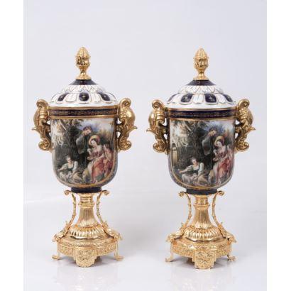 Pareja de jarrones en porcelana policromada, con asas dorada y pie circular estriado en bronce dorado, presentan escenas decorativas: