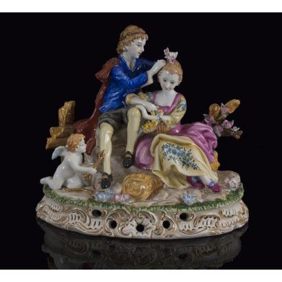 Bonita figura realizada en porcelana policromada, en ella contemplamos a una pareja de jóvenes en un entorno bucólico, el joven coloca una flor en el pelo de la chica mientras que Cupido los contempla sujetando una flecha dorada, símbolo del enamoramiento