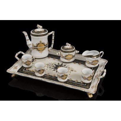 Porcelana. Original juego de café en porcelana en negro y dorado sobre fondo blanco, presenta asas imitando bambú,  consta de bandeja, cafetera, azucarero, jarra y tazas. Bandeja: 45x29cm. Cafetera: 19,5cm.