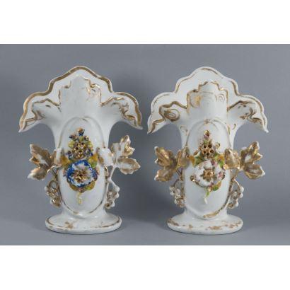 Porcelana. Pareja de violeteros en porcelana policromada, hacia 1900. Con decoración de flores con toques dorados. Numerada en la base. Medidas: 21 x 16 x 10 cm.