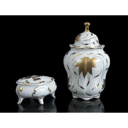 Porcelana. Bote y joyero en porcelana española, siglo XX. Piezas esmaltadas en blanco con decoración vegetal en oro. Marcadas en la base. Alturas bote: 17 cm. Largo joyero: 11 cm.