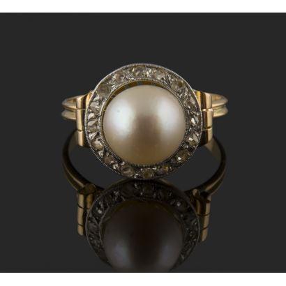 Elegante sortija en oro de 18K, presidida por una perla cultivada de 9,48 mm, orlada por 0,16 quilates de diamantes, con detalle tipo voluta en los hombros. Peso: 4,76 gr.