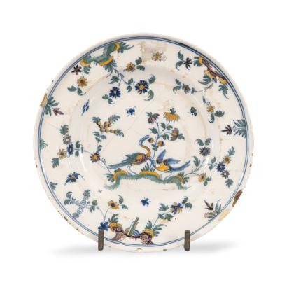 Plato en cerámica de Alcora, siglo XIX,  decorado con motivos vegetales y aves. Restaurado. Diámetro: 24cm.