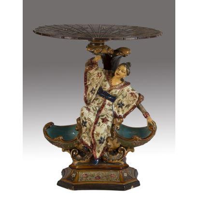 Figura realizada en cerámica esmaltada, en ella una mujer vestida con kimono sentada sobre un doble cuenco a modo de naveta, sujeta una especie de sombrilla a modo de tablero. Marca en base: W.S.S. Medidas: 40x18x22cm.