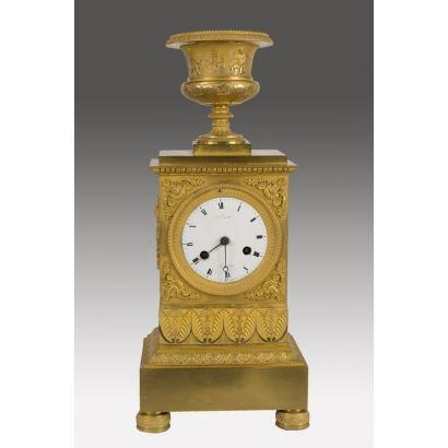 Relojes. Importante reloj de sobremesa IMPERIO, con forma de pedestal rectangular rematado con una copa, la pieza dorada en oro fino cuenta con esfera firmada: banset/b de la Cour/A. Bruxelles. s.XIX. 43x14x14cm.