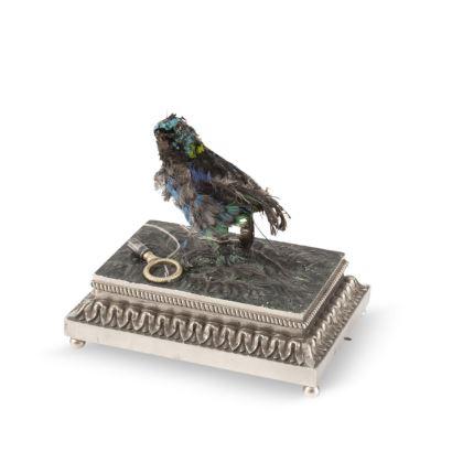 Caja de música con autómata, S. XIX. Realizada en metal plateado y parcialmente patinado. Presenta mecanismo de movimiento y canto de un pájaro. Medidas: 11,5x12, x9cm.