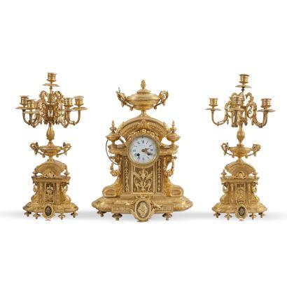 Reloj con guarnición, Luis XVI, S. XIX. Realizado en bronce dorado.  Decoración de palmetas, guirnaldas y rosetones. Medidas reloj: 50 x 37 x 17 cm. Medidas candelabros: 52 x 20x 10 cm.
