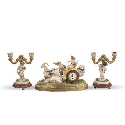 Reloj con guarnición, Francia S. XIX. En porcelana policromada con metal y madera policromada. Medidas reloj: 26 x 40 x 21 cm.  Medidas candelabros: 19 x 18,5 x 14 cm.