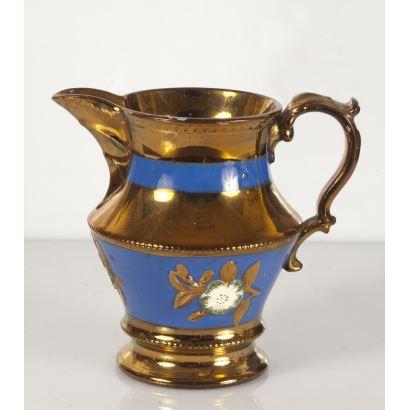 Magnífica jarra realizada en cerámica dorada de Bristol, con decoración de franjas azules con flores. 15x16cm.