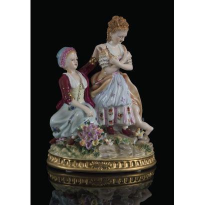 Curiosa figura de porcelana policromada, en ella vemos dos damas vestidas con amplios trajes, una de ellas se cubre y llama la atención dos piernas que salen de su falda. Marca en base. 26x19x14cm.