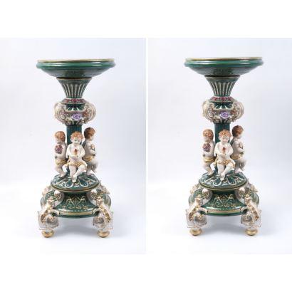 Pareja de peanas realizadas en porcelana policromada y esmaltada, con decoración sobre fondo verde y tablero circular con escena de concierto. Medidas: 77x35cm.