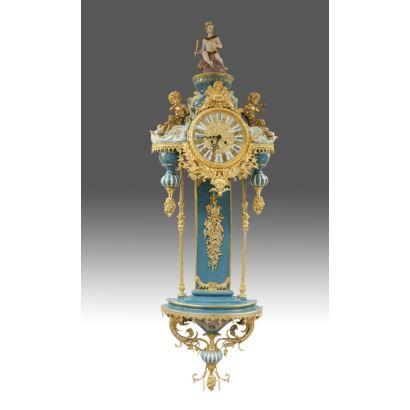 Excepcional reloj de pared en porcelana policromada en azul y blanco, con apliques en bronce dorado, rematado por figura de Rey. Medidas: 150x50cm.