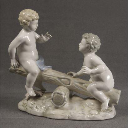 Bella figura realizada en porcelana policromada en la que encontramos una representación de gusto clasicista en la que vemos a dos niños sobre un balancín. Marca en base. 19x17x9cm.