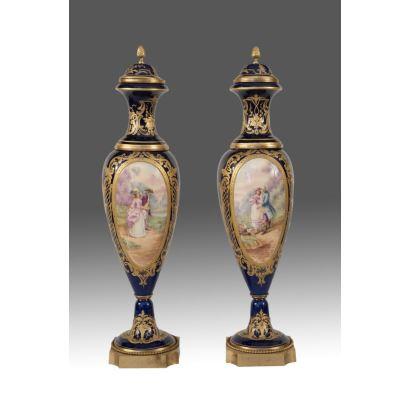 Magnífica pareja de jarrones Sèvres, con tapa en porcelana policromada sobre fondo azul cobalto, presentan escenas galantes y paisajes en medallones y motivos dorados. Siglo XIX. Alto: 55cm.