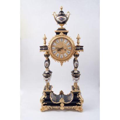 Gran reloj de sobremesa con péndulo, en porcelana policromada en azul y blanco con apliques en bronce dorado, consta de dos cuerpos unidos por cuatro columnas, rematado en copa. Medidas: 103x43x23cm.