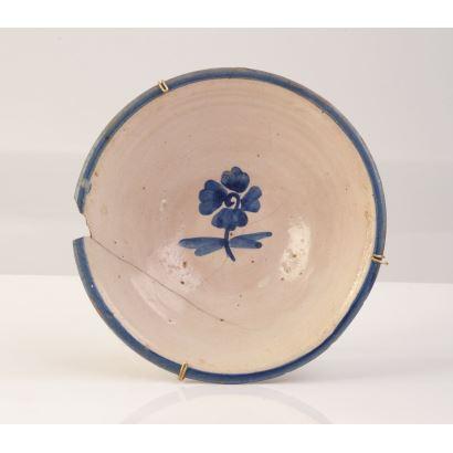 Antiguo cuenco realizado en cerámica esmaltada, con decoración floral azul en fondo. Presenta desperfectos. Diámetro: 19cm.