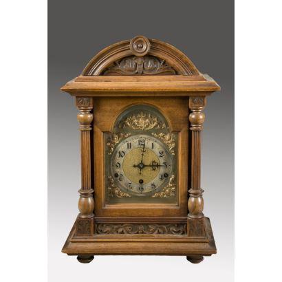 Bello reloj de sobremesa de Carrillón con cinco martillos, cuenta con bella estructura de madera flanqueada por dos columnas clasicistas. (Necesita repaso). 46x32cm.
