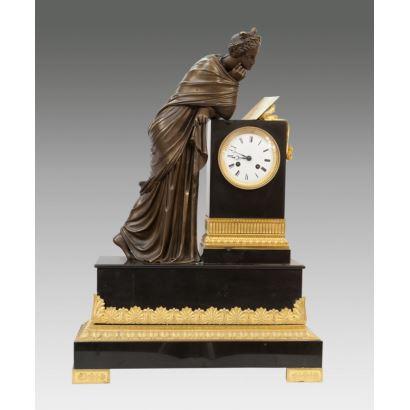 Reloj de sobremesa francés de estilo Imperio, con peana de mármol negro y bronce al oro fino, decorada en bulto redondo con mujer clásica leyendo apoyada en peana que alberga la esfera. Medidas: 62x44x16cm.