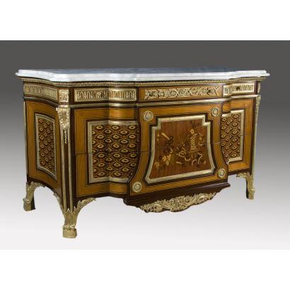 Cómoda estilo transición realizada en marquetería, tablero de mármol y apliques de bronce dorado, faldón con tres cajones y dos cajones inferiores de mayor tamaño. S.XX.  Medidas: 98x176x70cm.