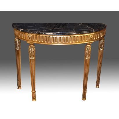 Consola realizada en madera tallada y dorada con tablero semicircular en mármol, presenta cuatro patas rectas estriadas con motivos vegetales. Estilo Luis XVI, s. XX.  Medidas: 86x112x51cm.