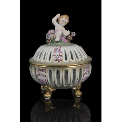 Bombonera esférica calada realizada en porcelana policromada, rematada en tapa con imagen de niño entre flores. Medidas: 23,5x18cm.