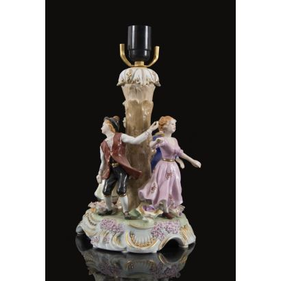 Lámpara realizada en porcelana policromada, representa a un grupo de niños jugando entorno a árbol. Marca en base. 36x18x18cm.