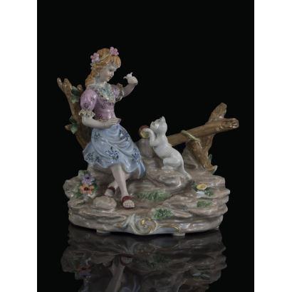 Bonita figura en porcelana policromada, en ella una niña sentada sobre una madera  juega animadamente con un gato. Marca en base. 22x20cm.