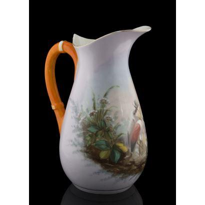 Magnífico aguamaníl de porcelana, con bonita decoración de aves entre vegetación, destaca el asa de color naranja. Altura: 32cm.