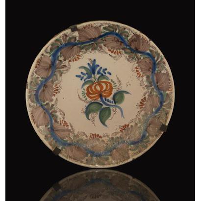 Plato de cerámica de Manises s.XIX, con flor naranja en parte central y motivos vegetales marrones en borde. Presenta leves desperfectos. Diámetro: 30cm.