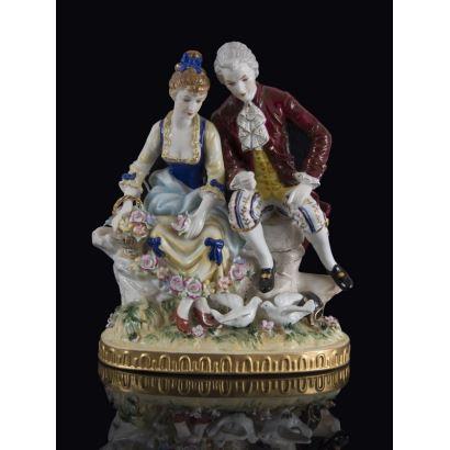 Bonita figura en porcelana policromada, con escena galante de dos personajes sobre un banco que contemplan palomas. Marca en base. 24x24x12cm.