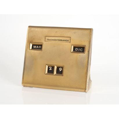 Calendario de sobremesa, siglo XX. Trasmediterranea. Caja en metal dorado. Marca día y mes. Medidas: 11 x 11 cm.