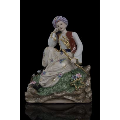 Figura en porcelana policromada en la que contemplamos a un personaje masculino oriental sentado en actitud pensativa sobre rocas, sujeta un sable dorado. Medidas: 36x27x16cm.
