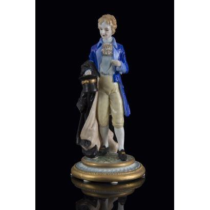 Figura de porcelana policromada en la que contemplamos la imagen de un elegante caballero vestido a la moda francesa, sujeta un abrigo y un sombrero de copa alta con el brazo.  22x32x15cm.