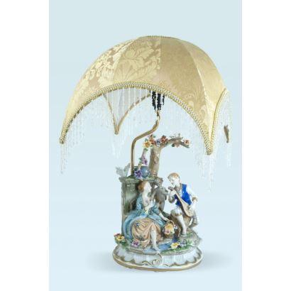 Lámpara de mesa en porcelana esmaltada y policromada, siglo XX. Decoración de figuras al estilo dieciochesco. Escena galante con querubín. Marcada en la base. Medidas: 52 x 26 x 20 cm.