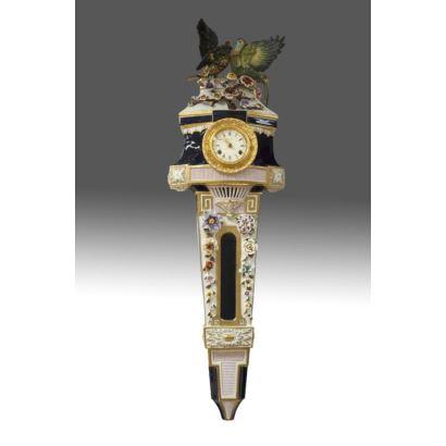 Reloj de pared realizado en porcelana policromada y bronce dorado,  la caja en el cuerpo superior está coronada por figuras de aves en relieve sobre flores y cuerpo inferior rematado en estípite, en azul cobalto y blanco. Medidas: 95x30cm.