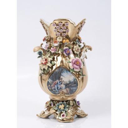 Jarrón en porcelana dorada con ricos motivos florales de colores diversos  y escena galante en medallón. Marca en base. Medidas: 34,5x20cm.