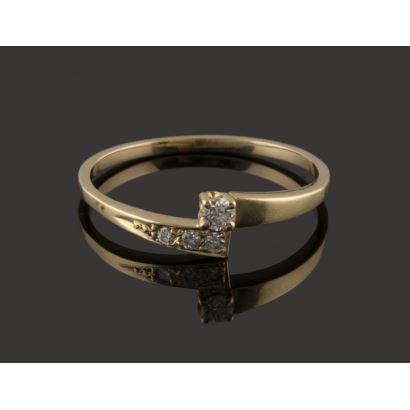 Bonita sortija en oro amarillo de 18K. Hombros cruzados en el centro a diferente altura, uno de los cuales se ornamenta con un carril de 3 diamantes,  y el otro se remata con un diamante de 0,06 quilates, engarzado en garras. Peso: 1,48 gr.